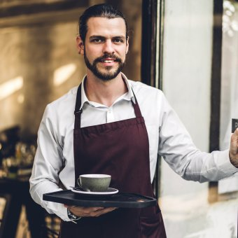 Portrait of handsome bearded barista man small business owner smiling and holding cup of coffee outside the cafe or coffee shop.Male barista standing at cafe